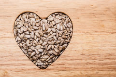 Heart shaped sunflower seeds on wood surface Royalty Free Stock Photography
