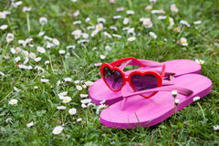 Heart shaped sunglasses and flip flops in the grass Stock Image