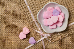 Heart-shaped sweets on sack tablecloth Stock Image