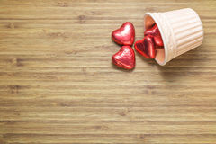 Heart shaped sweets wrapped in a bright red foil lying in a ceramic vase on a wooden texture. Background for romantic themes. Royalty Free Stock Photos
