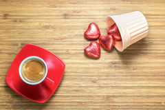 Heart shaped sweets wrapped in a bright red foil lying in a ceramic vase on a wooden texture with red cup of coffe near it. Stock Images