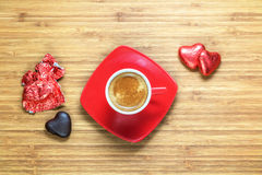 Heart shaped sweets wrapped in a bright red foil lying on a wooden texture with red cup of coffe near it. Stock Photography