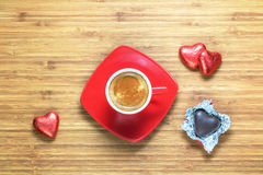 Heart shaped sweets wrapped in a bright red foil lying on a wooden texture with red cup of coffe near it. Royalty Free Stock Photography