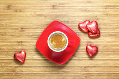 Heart shaped sweets wrapped in a bright red foil lying on a wooden texture with red cup of coffe near it. Stock Image