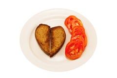 Heart-shaped toast and tomato Royalty Free Stock Photography