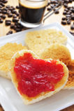 Heart-shaped toasts with jam. A plate with some heart-shaped toasts with strawberry jam with a cup of coffee and coffee beans in the background Royalty Free Stock Photo