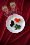 Heart shaped toasts with red and black caviar and two glasses of champagne on white plate on red drapery Royalty Free Stock Photography