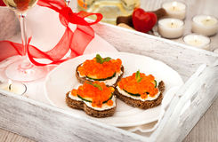 Heart shaped toasts with red caviar and white wine. On tray-Valentine concept royalty free stock photography