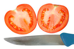 Heart-shaped tomato and a knife. Sliced tomato in the shape of heart and a knife. Association with the parting, unrequited love, separation, machinations Royalty Free Stock Images