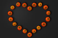 Heart Shaped Tomatoes. Heart shaped cherry tomatoes isolated over a black background with clipping path royalty free stock image