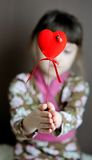 Heart shaped toy with ladybird in child's hands Royalty Free Stock Images