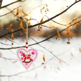 Heart shaped Valentines or Christmas decoration toy hanging on the tree branch with snow on the background Royalty Free Stock Images