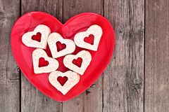 Heart shaped Valentines Day cookies on a red heart plate over wood Stock Image