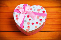 Heart shaped Valentines Day gift box on wooden background. Royalty Free Stock Images