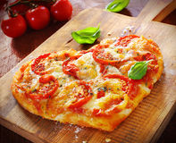 Heart shaped vegetarian pizza. Topped with cheese and tomato on an old wooden board signifying love of pizza, or romantic love for Valentines day or an Royalty Free Stock Photo