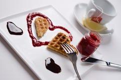 Heart shaped waffle, marmalade, chocolate sauce, vanilla sticks,. A heart shaped waffle on a heart shaped berries sauce and a chocolate sauce heart on a square Stock Photo