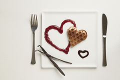 Heart shaped waffles, marmalade, chocolate sauce, vanilla sticks. A heart shaped waffle on a heart shaped berries sauce reduction and a chocolate sauce heart on Royalty Free Stock Photography