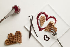 Heart shaped waffles, marmalade, chocolate sauce, vanilla sticks. A heart shaped waffle on a heart shaped berries marmalade heart on a square plate garnished Royalty Free Stock Image