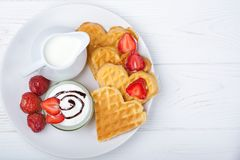 Heart shaped waffles with strawberries, cream sauce, pitcher with milk on white plate and white background. stock image