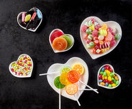 Heart shaped white bowls filled with hard candies Stock Photos