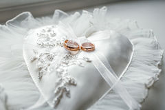 Heart-shaped pillow with lace wedding gold rings Royalty Free Stock Image