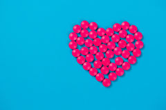 Heart shaped of white pills on blue paper background. Top view Royalty Free Stock Photo