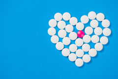 Heart shaped of white pills. On blue paper background, top view Stock Images