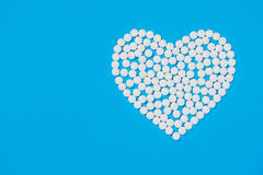 Heart shaped of white pills. On blue paper background, top view Royalty Free Stock Image