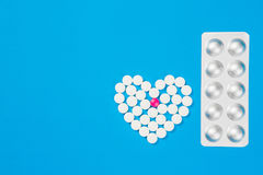 Heart shaped of white pills on. Blue paper background, top view Royalty Free Stock Photo