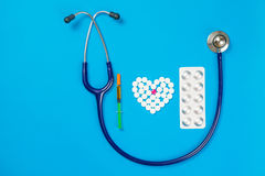 Heart shaped of white pills and medical tool. On blue paper background, top view Stock Images
