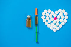 Heart shaped of white pills and syringe on blue paper background. Top view Royalty Free Stock Photography