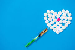 Heart shaped of white pills and syringe. On blue paper background, top view Stock Image