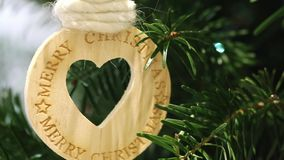 Heart shaped wooden Christmas decoration object on a Christmas tree. With shining spotlights stock footage