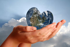 Heart shaped world in young womans hands Royalty Free Stock Photo