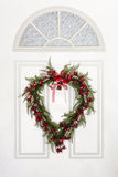 Heart Shaped Wreath Hanging on White Door. Heart shaped door wreath on white Colonial style door.  Made up of tiny red and pink flowers with fern greenery and Royalty Free Stock Image