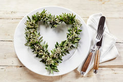 Heart shaped wreath over white dish. Table setting decorated with green and white wreath in shape of heart over white dish and cutlery set on napkin. Old wooden Royalty Free Stock Image