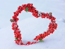 Heart-shaped wreath of red berries in the snow as a greeting for Royalty Free Stock Photos