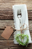 Heart Shaped Wreath and Wedding Cutlery on White Napkin. High Angle Close Up of Silver Wedding Knife and Fork Tied with String and Blank Tag on White Napkin with Royalty Free Stock Images