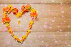 Heart shaped yellow and orange flowers on vintage wooden background Stock Image