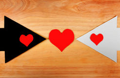 Heart Shapes and the Arrows. Heart Shapes on the Black and White Arrows on the Wooden Background Stock Photos