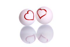 Heart shapes drawn on eggs. Heart shape drawn on two eggs , representing as couple and  placed over mirror reflection, isolated against white background Royalty Free Stock Photography