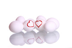 Heart shapes drawn on eggs. Heart shape drawn on two eggs , representing as couple and surrounded by other eggs  , placed over mirror reflection, isolated Stock Photography