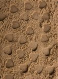Heart shapes made on the sand background. In view stock image