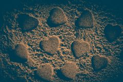 Heart shapes made on the sand background. In view royalty free stock photos