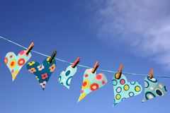 Heart shapes on washing line. Close up of colorful, patterned heart shapes on washing line, blue sky background Stock Photos
