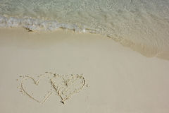Heart shapes on white sand beach Royalty Free Stock Photo