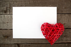 Heart with sheet of paper on a wooden board. Royalty Free Stock Photos