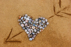Heart of shells pierced by an arrow. Royalty Free Stock Image