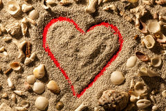 Heart and shells. Sand with red background. A heart drawn in the sand. Red background. Around the heart numerous shells Mexican stock photos