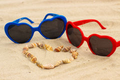 Heart of shells and sunglasses on sand at the beach Stock Image